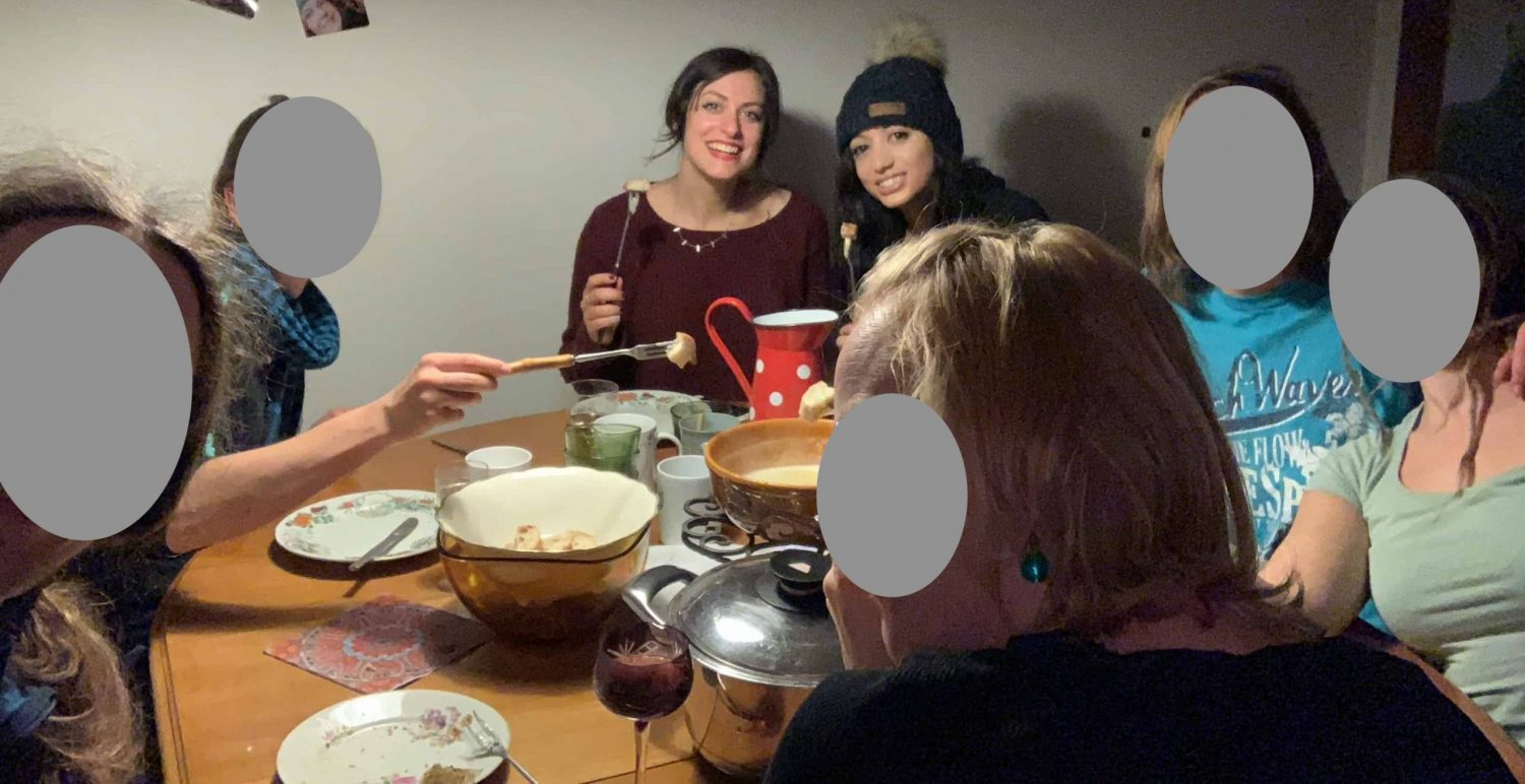 People sitting around a table, eating fondue