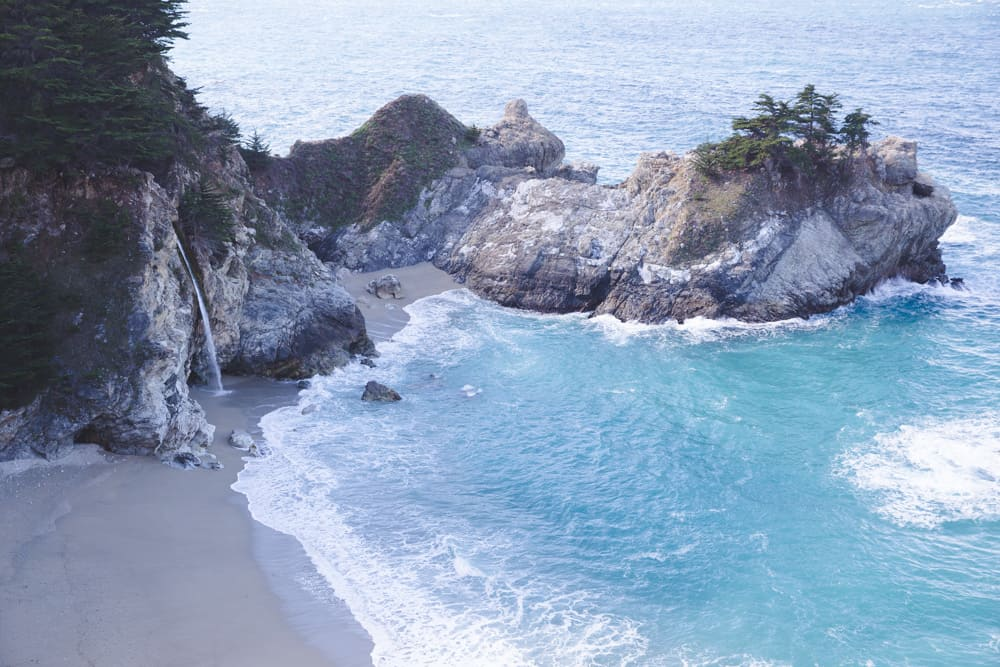 McWay Falls in Big Sur, California is a waterfall on the beach that pours into the bright blue ocean on my California Travel Bucket List