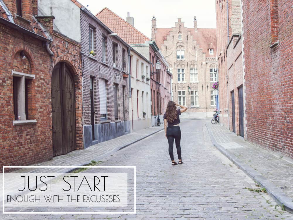 Girl standing on cobblestone street in Bruges, Belgium surrounded by brick houses and buildings