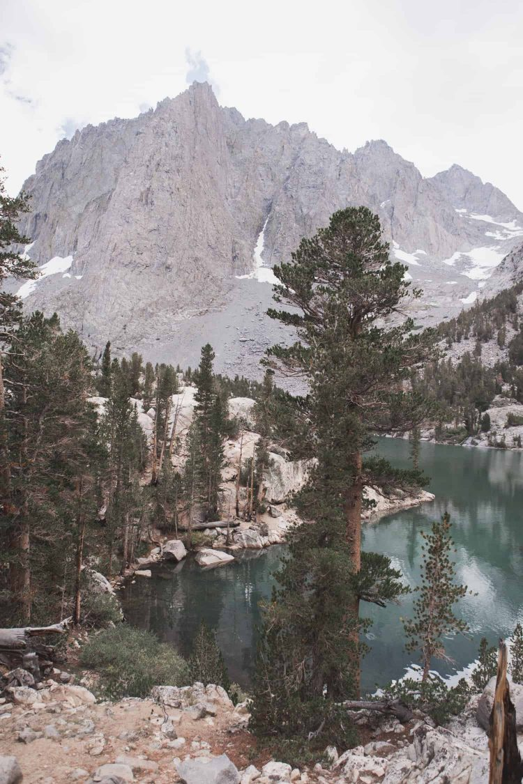 Third Lake in the Big Pine Lakes Trail in the Eastern Sierras is a blue lake with pine trees and mountains