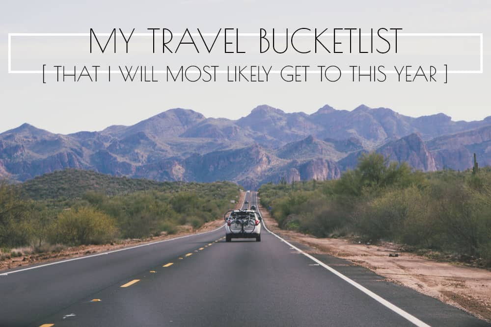 Car driving down a road with mountains in the background in Arizona - This list is a California travel bucket list