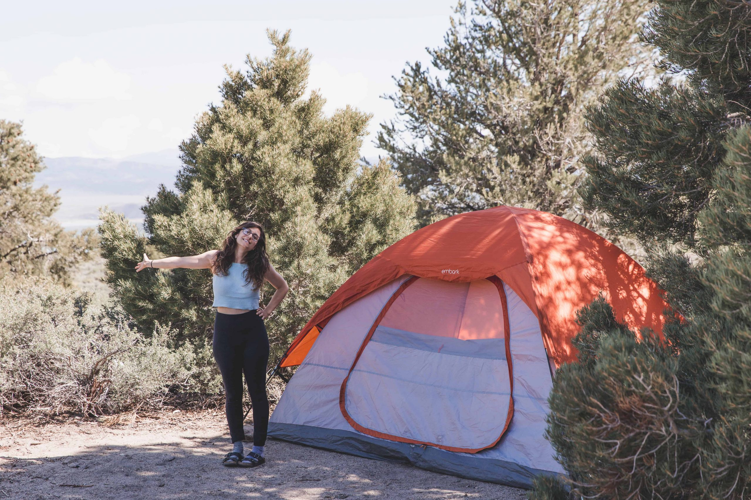 Kelsey in front of an orange tent camping near Mono Lake in Mammoth, California in the Eastern Sierras camping for free in California