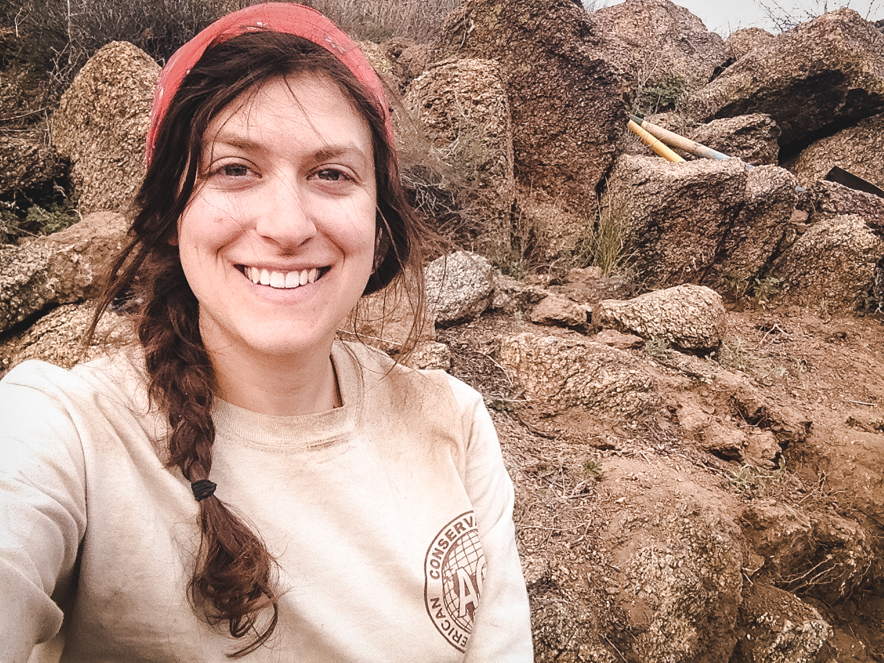 Kelsey outside in the desert, smiling at the camera in the conservation corps