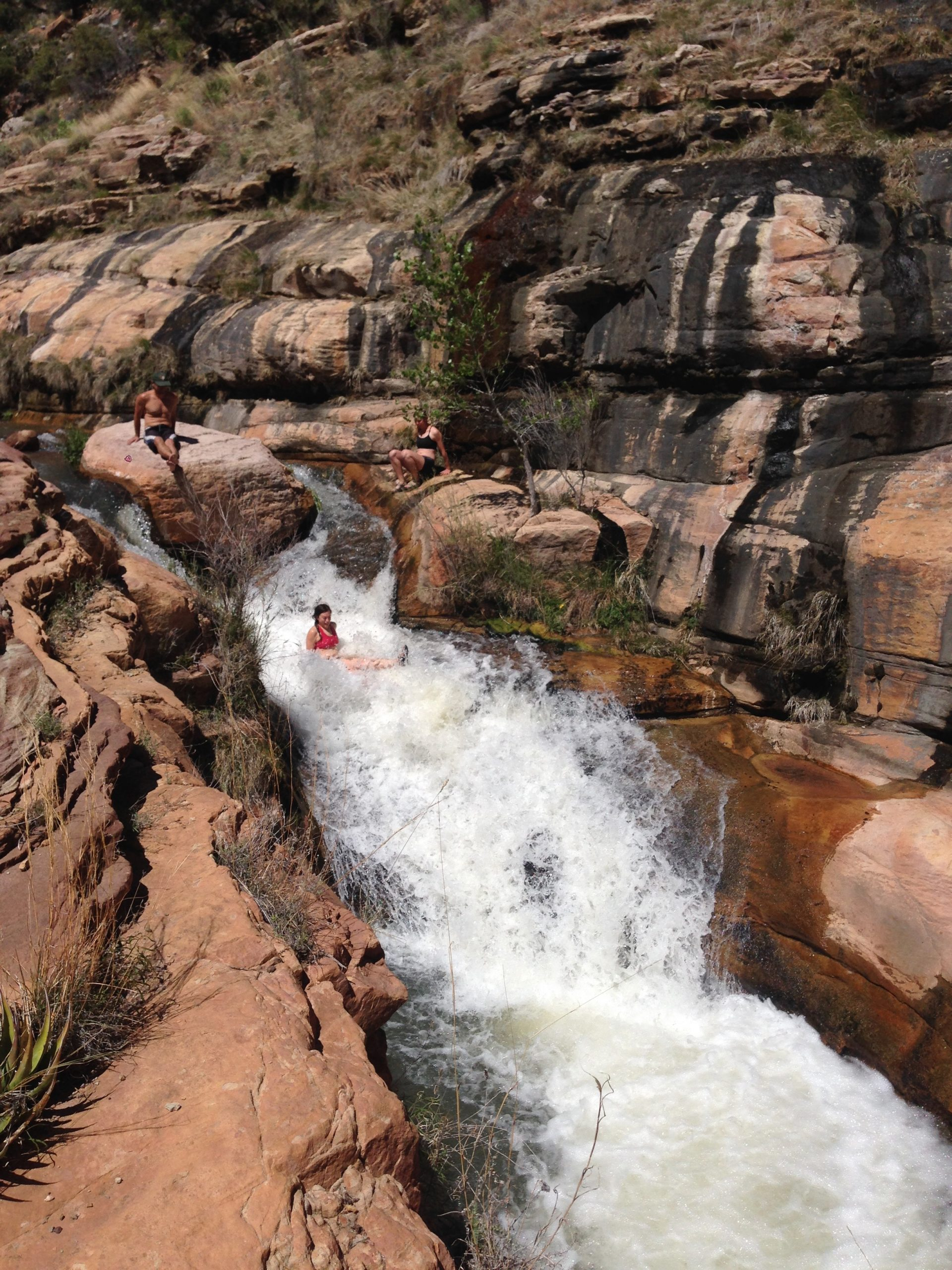Sliding down a natural water slide in the Grand Canyon