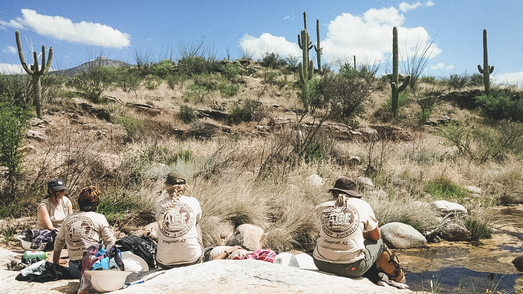 4 conservation corps members taking a break from work in Saguaro National Park, sitting around a rock in the hot sun with the desert in the background