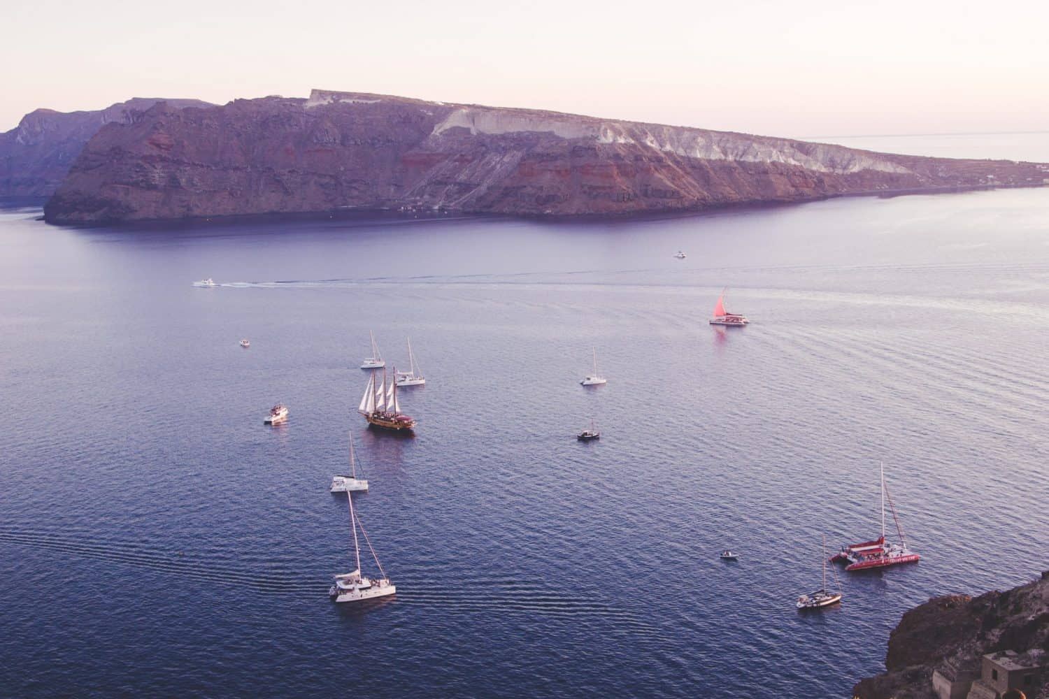 Boats on the water in Santorini during the sunset in Oia