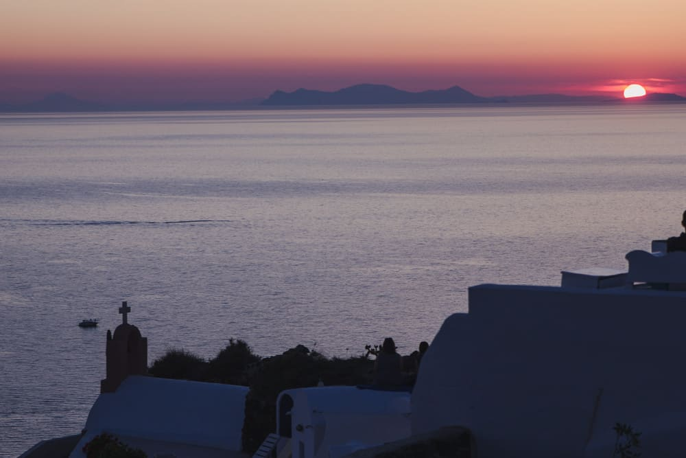 Sun sinking into the ocean at the sunset in Oia, Santorini - Santorini is an unexpectedly perfect place for solo female travelers