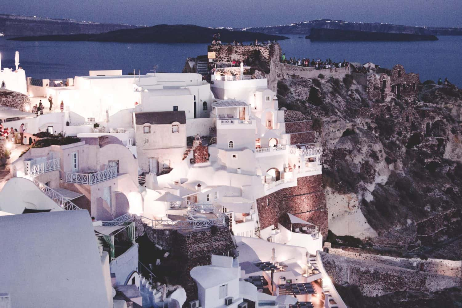 Oia at night in Santorini, Greece. Oia is full of beautiful white buildings perched on a rocky volcanic cliff.