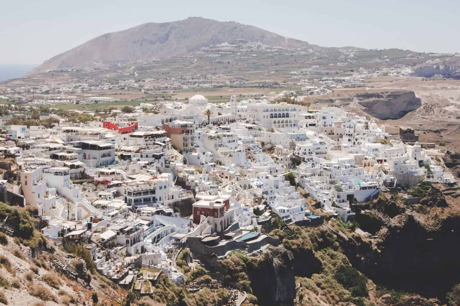 The Greek island of Santorini is on a volcanic cliff with lots of white buildings.