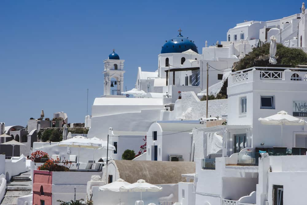 Caldera views of white buildings and blue domed churches in Santorini - Santorini is a perfect destination for solo female travelers!