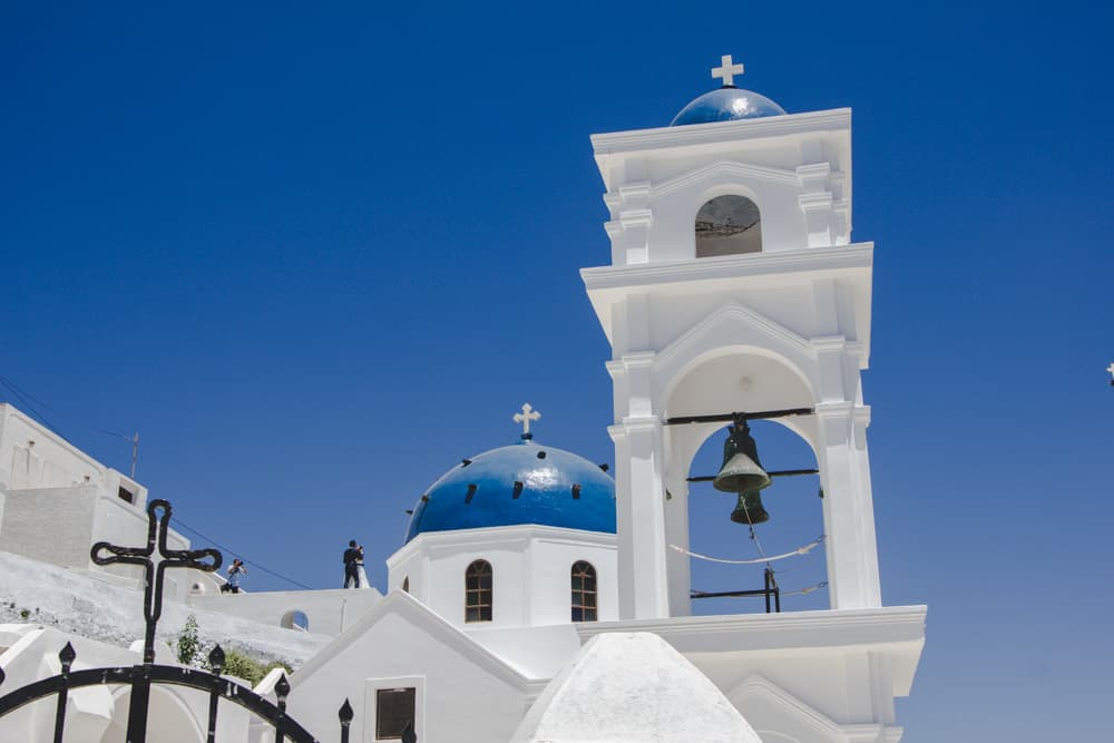 Blue domed churches and white buildings in Santorini, Greece - Santorini is a perfect destination for solo female travelers!