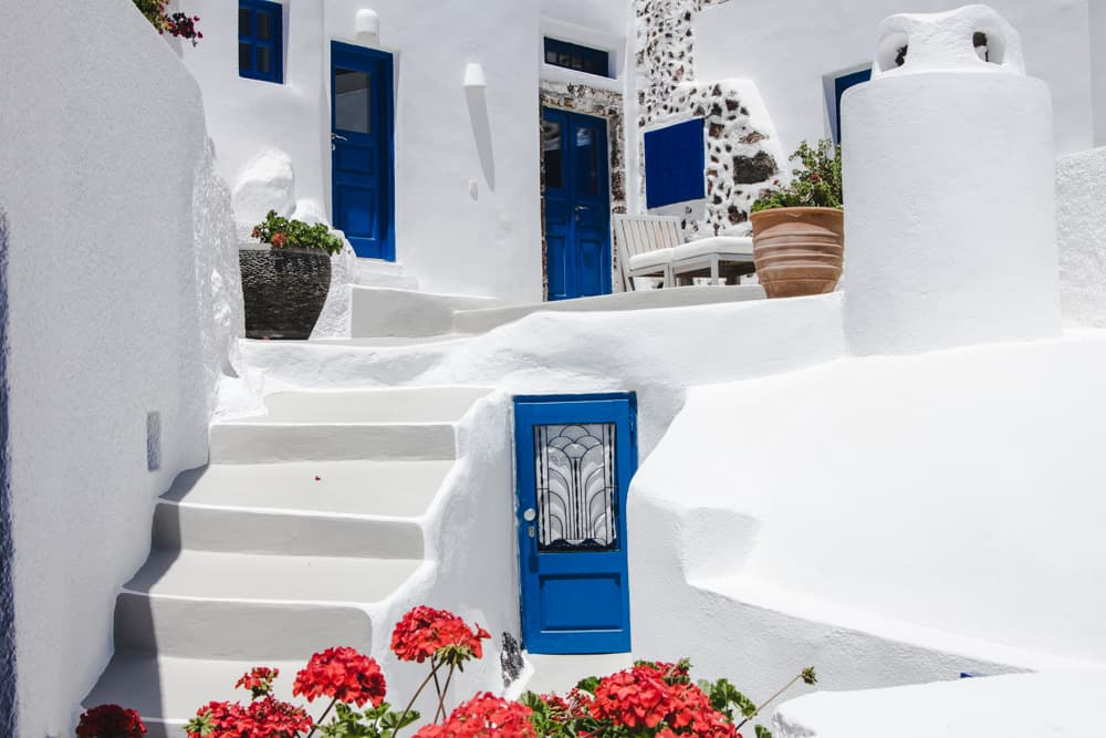 Blue doors and white buildings in Santorini, Greece - Santorini is a perfect destination for solo female travelers!