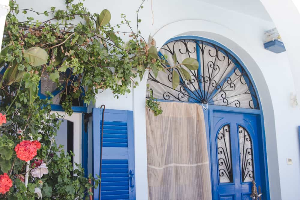 Iconic blue doors, white buildings, and red flowers in Santorini, Greece - Santorini is a perfect destination for solo female travelers!
