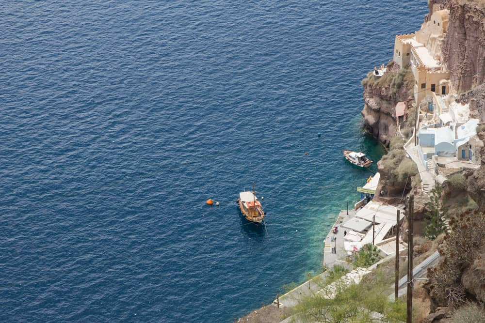 Boat on blue water near the cliffs in Santorini, Greece - Santorini is a perfect destination for solo female travelers!