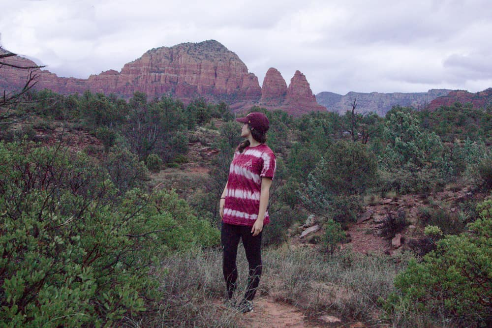 Woman staring at red rocks in Sedona, Arizona surrounded by junipers and bushes