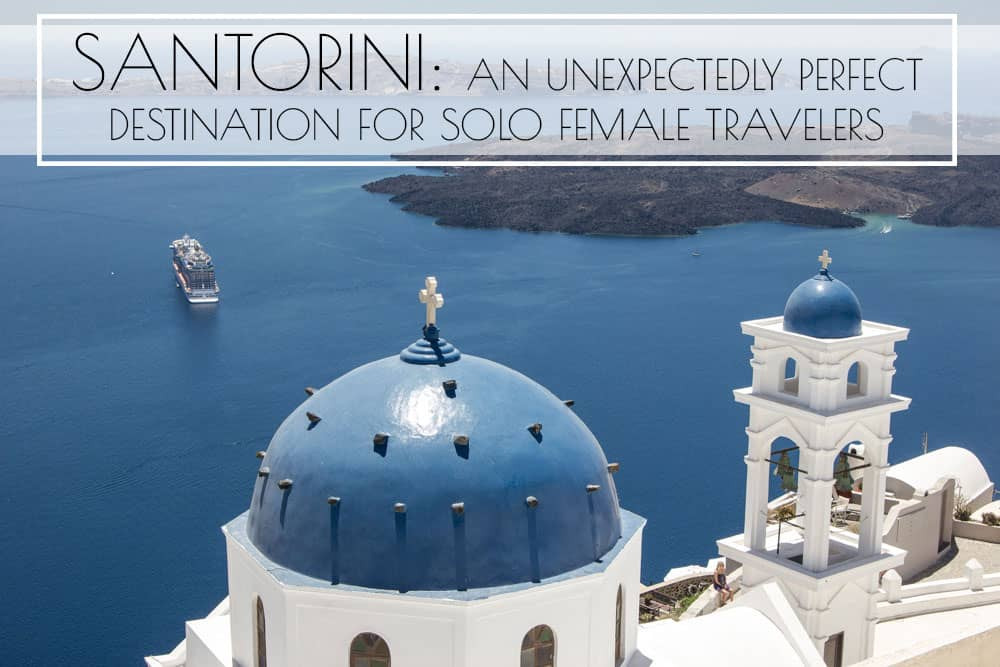 View from Santorini caldera of a blue domed church and ferry on water - Santorini is a perfect destination for solo female travelers!
