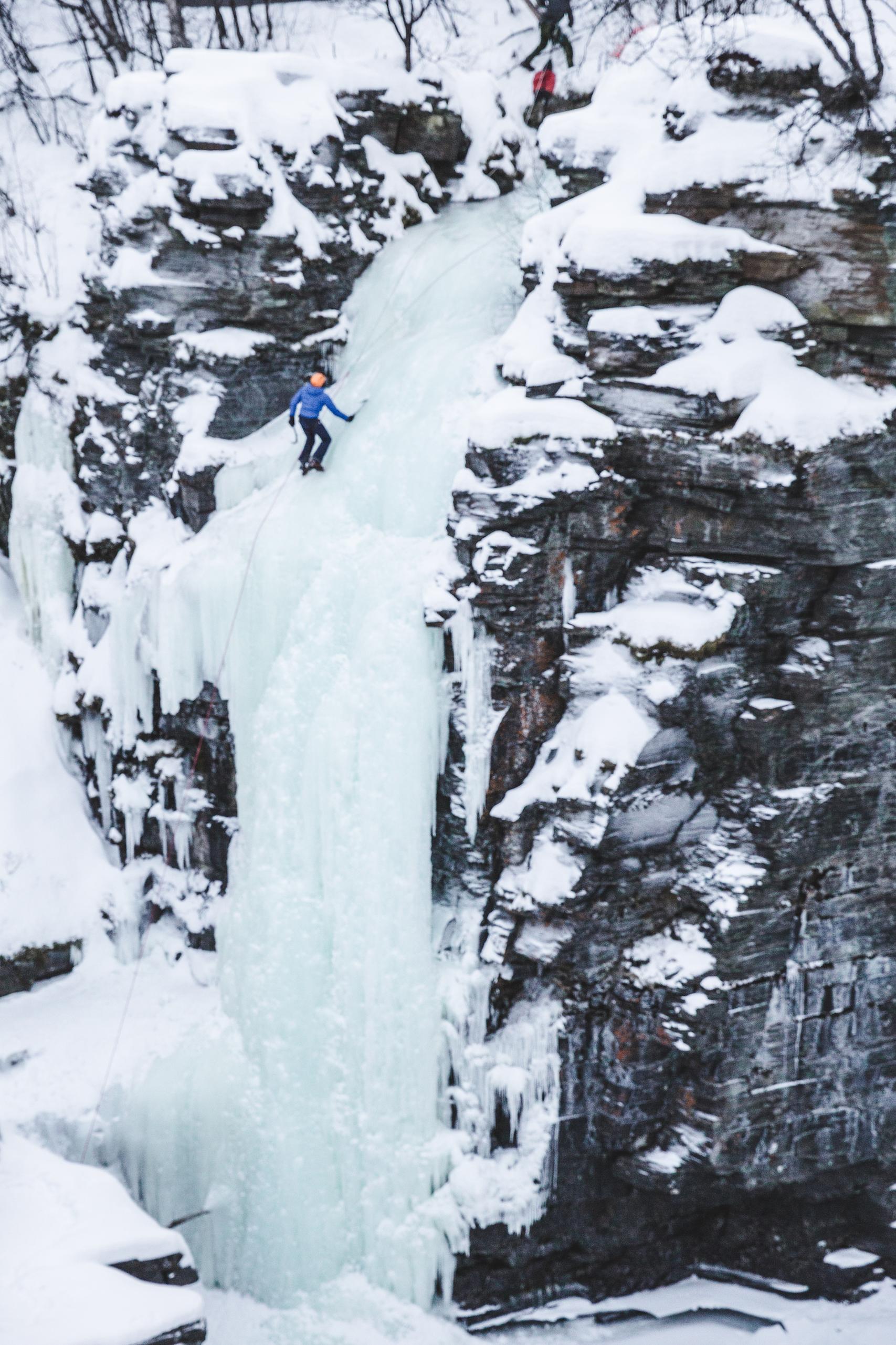 Person climbing frozen waterfall in Abisko, Sweden in winter