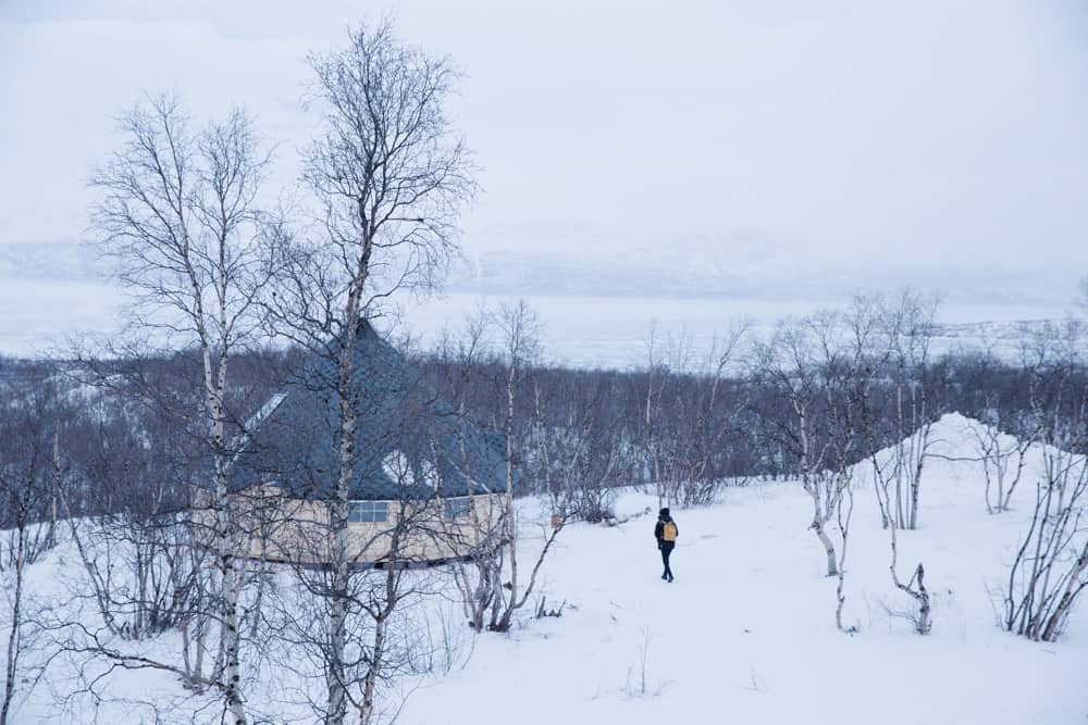 Frozen Lake and snow around a yellow building in Abisko, Sweden in January