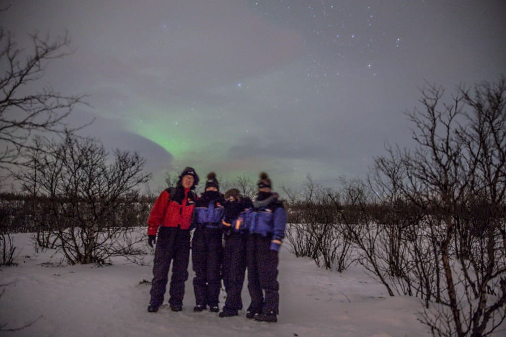 Friends standing in front of the green Northern Lights in Abisko, Sweden