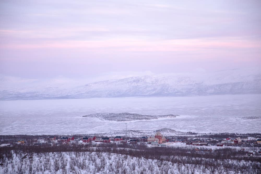 Views of the frozen lake, snowy landscape, and red houses from Stornabben in snow covered Abisko, Sweden in January