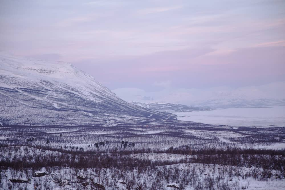 Views of the frozen lake, snowy landscape, and mountain from Stornabben in snow covered Abisko, Sweden in January