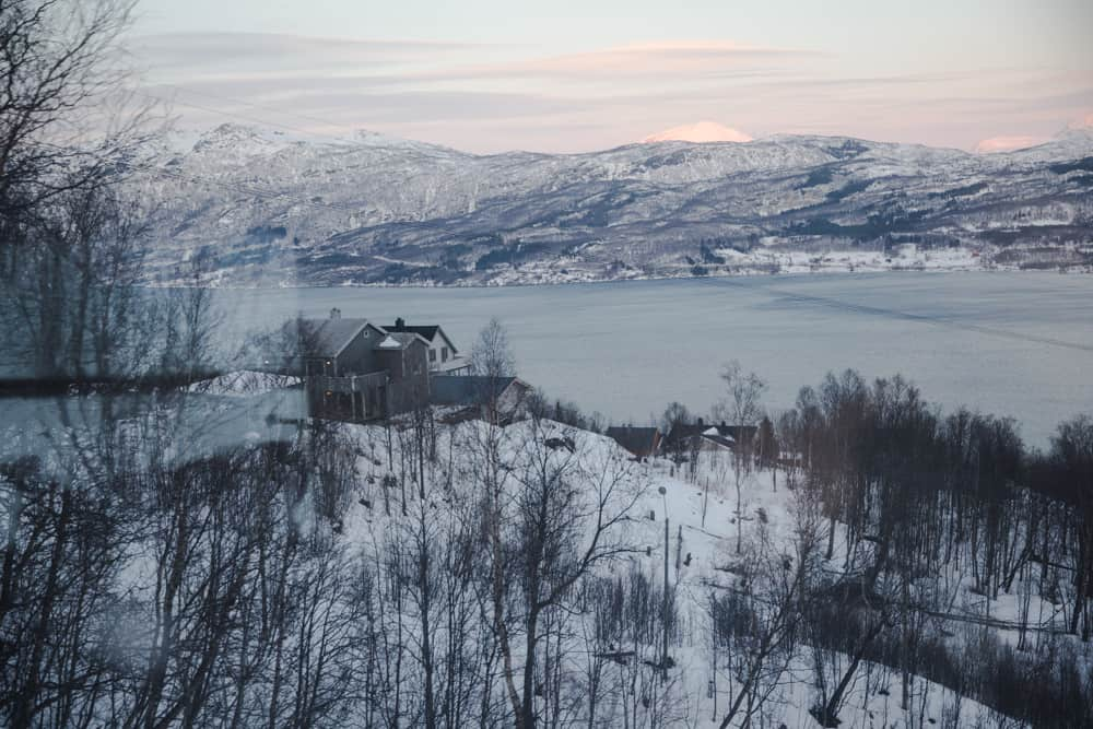 Fjord in Narvik, Norway full of light blue water and surrounded by a snowy landscape of trees and one house.