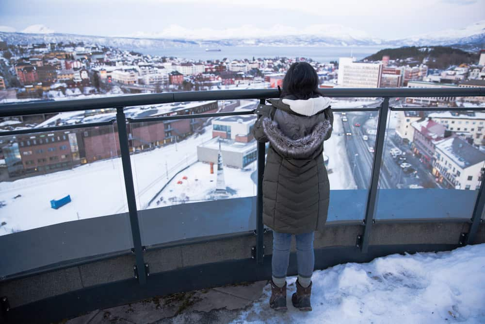 Looking out at the snow covered landscape of colorful buildings and a fjord in Narvik, Norway
