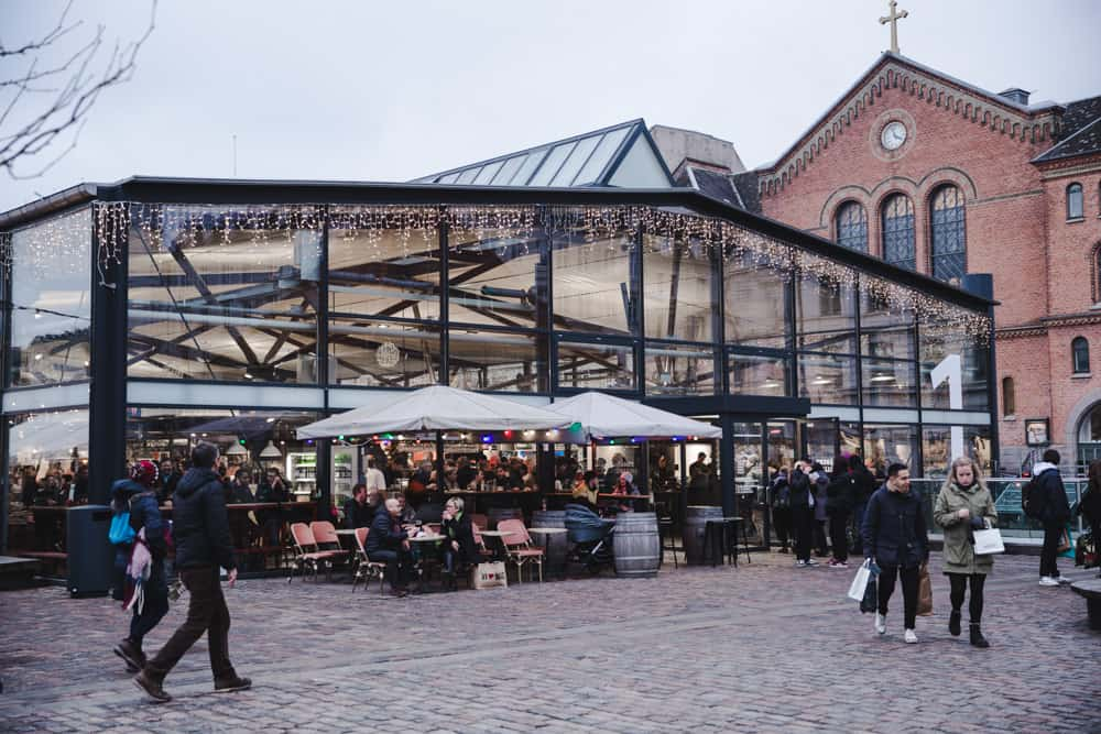 The Torvehallerne Markets are glass buildings that sell different foods in Copenhagen, Denmark. People walk by them in the winter.