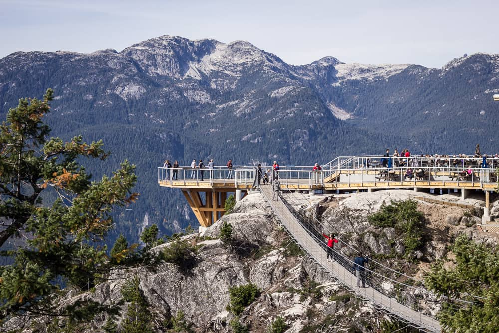 People crossing a suspension bridge at the Sea to Sky Gondola in the mountains of Squamish near Vancouver, Canada