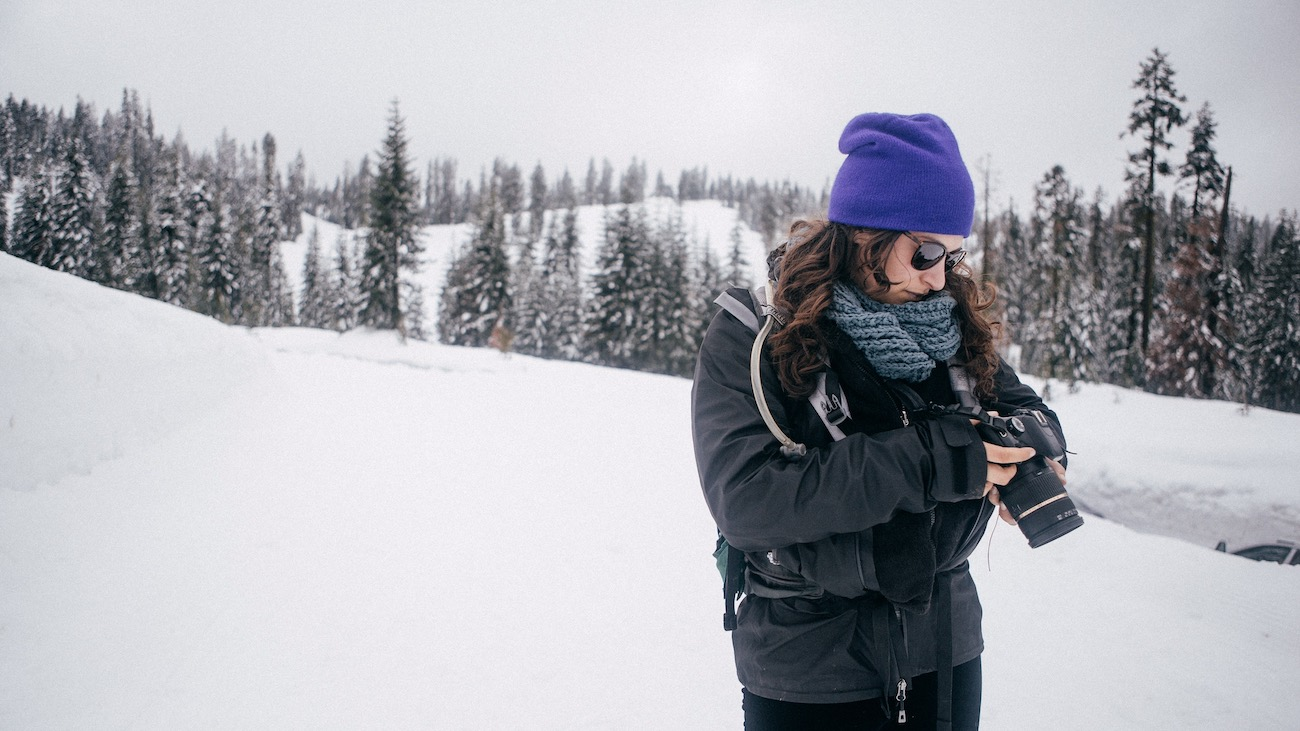 Kelsey looking at her camera in the snow in Yosemite in winter