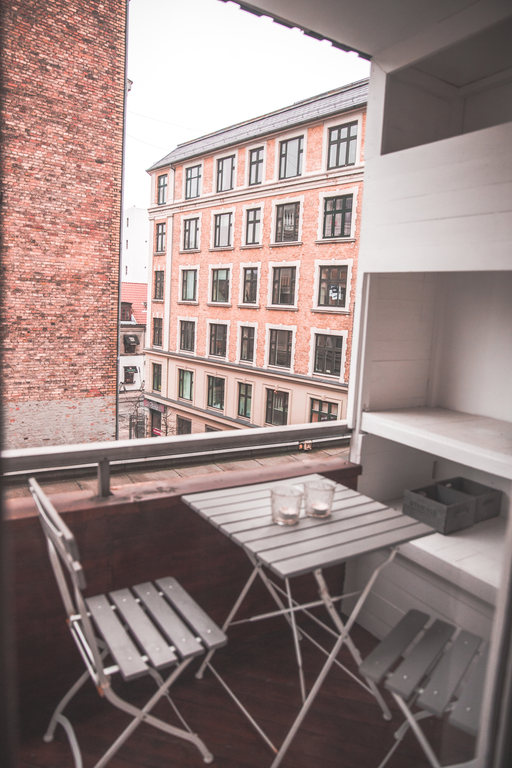Copenhagen AirBnb Deck with chairs and a table and view of other buildings