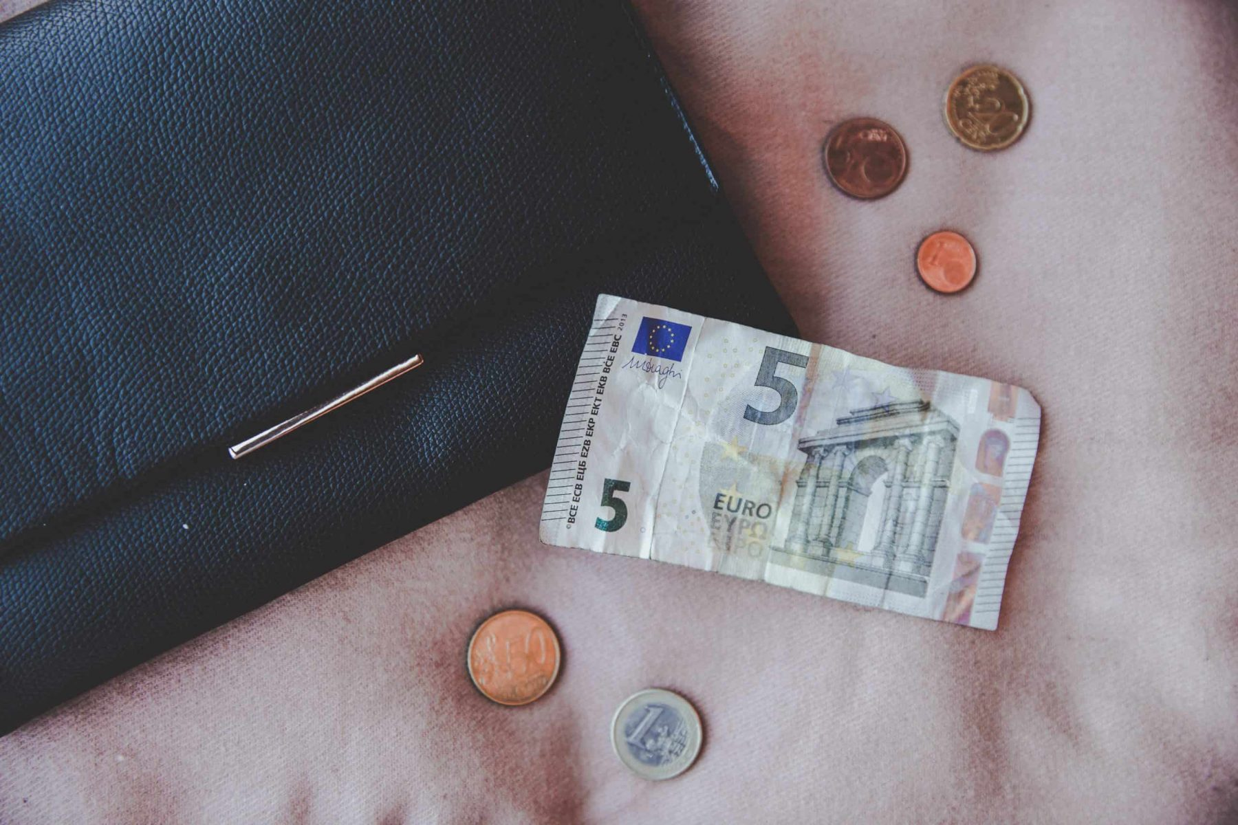 Euros next to a purse - I spend much less money as a digital nomad!