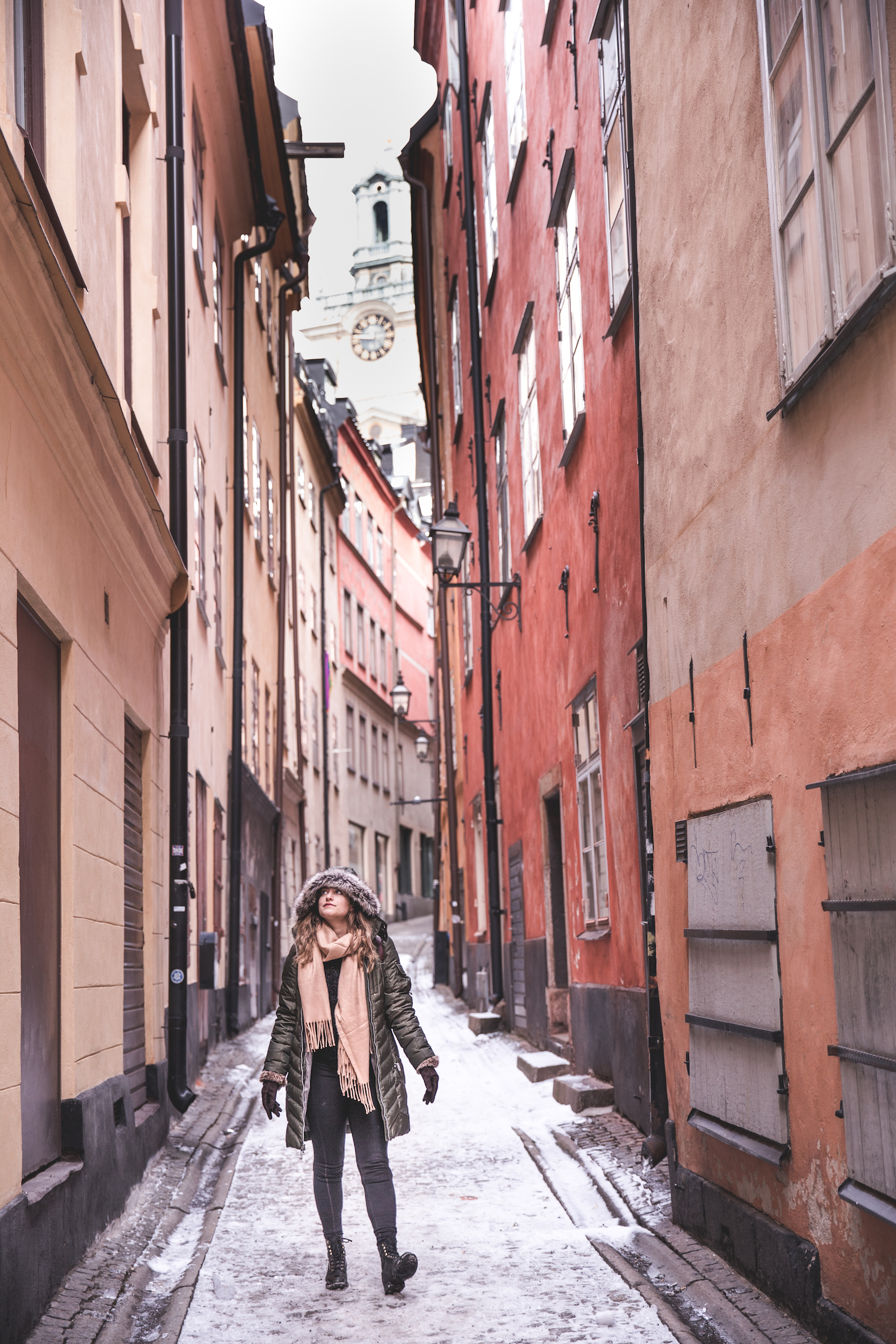 Kelsey wearing winter clothes and walking in an alley in the Stockholm Old Town, Gamla Stan, surrounded by bright red and orange buildings with snow on the ground