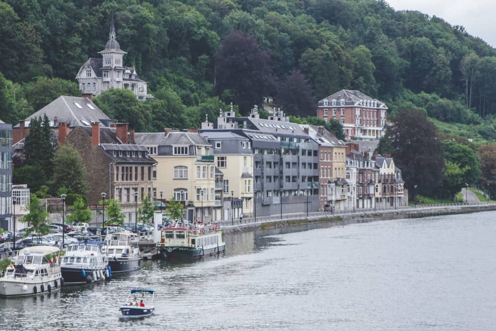 Boat on the river in Dinant in Belgium surrounded by trees and beautiful buildings