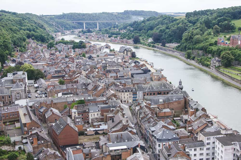 View of Dinant city buildings, rooftops, river, and bridge from the stairs up to the Citadelle de Dinant, or Citadel of Dinant in Belgium