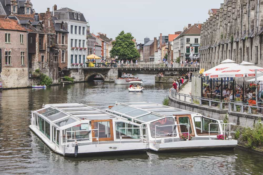 Boast in a canal in Ghent, Belgium surrounded by walkways, bridges, and brick buildings