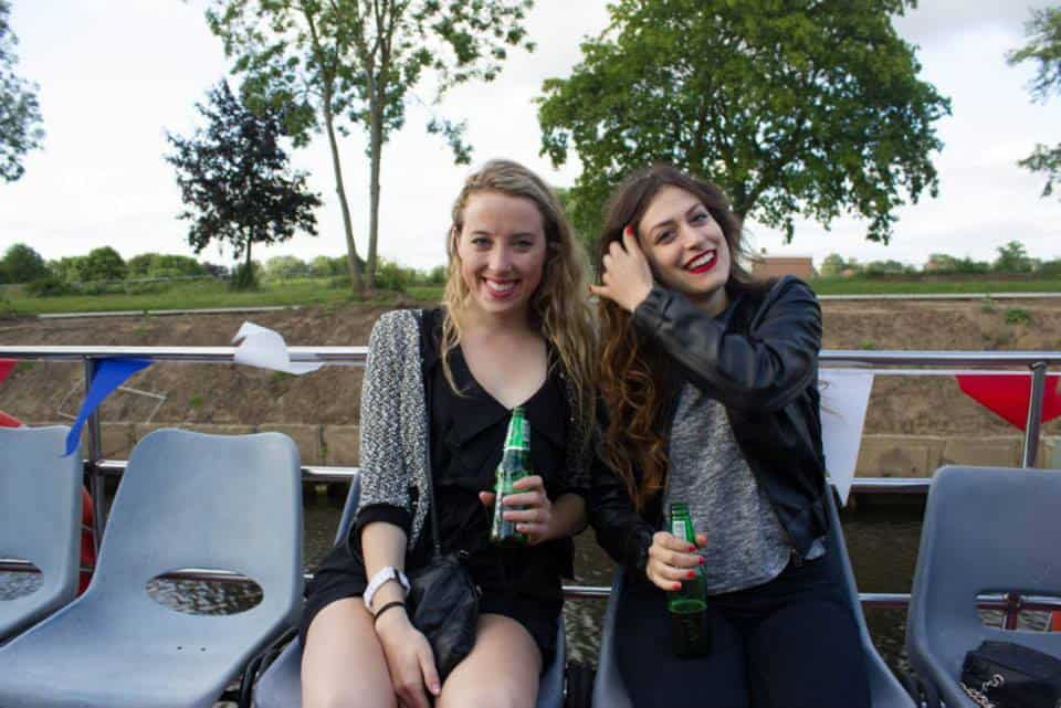 Two girls drinking beer on a boat on the river in York in England
