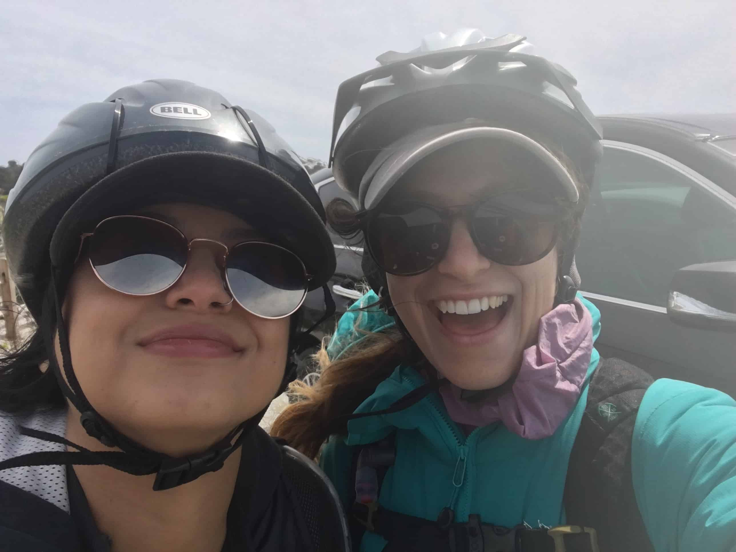 Two smiling girls with bike helmets on their bike ride along the 17-Mile Drive in Monterey, California