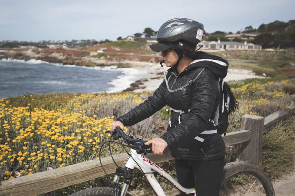 A girl on a bike drinking water from a CamelBak hydration bladder with the ocean behind her on the 17-Mile Drive in Monterey, California