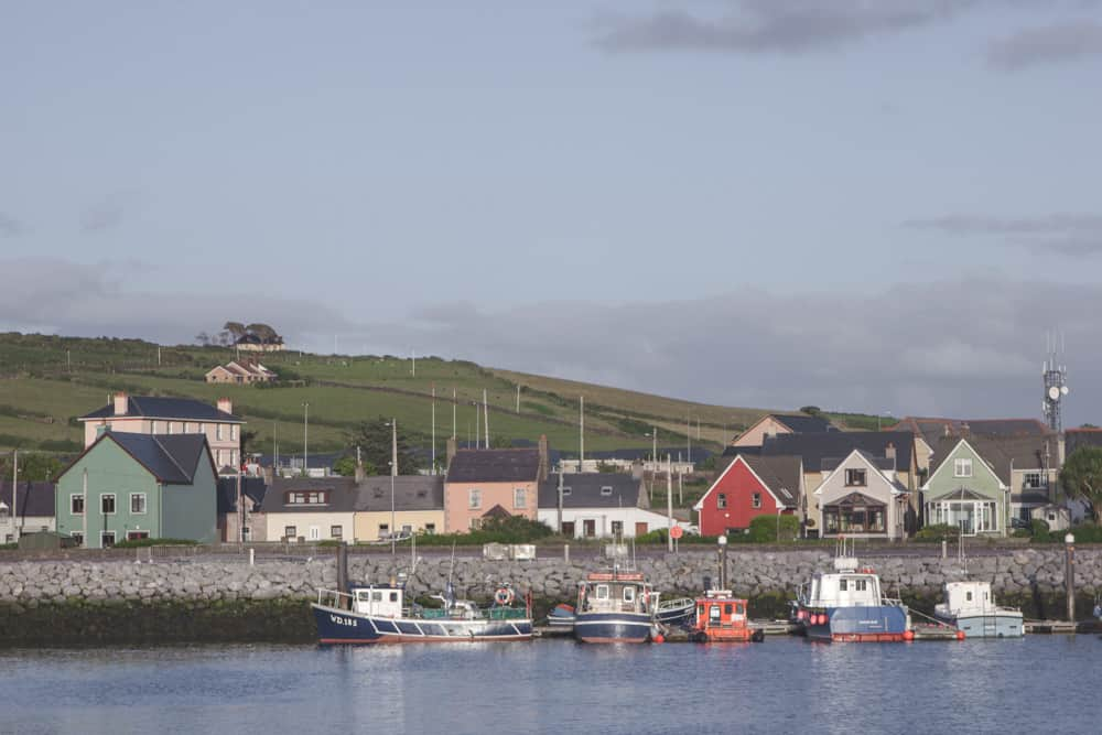 The Dingle Harbor in Ireland has a scene of rolling grassy hills, brightly colored buildings, and boats