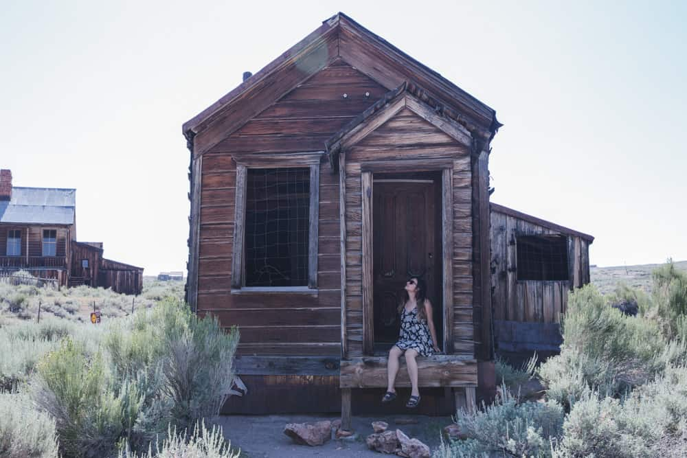 Kelsey sitting on the porch of an old wooden house in Bodie State Historical Park, a famous ghost town in California