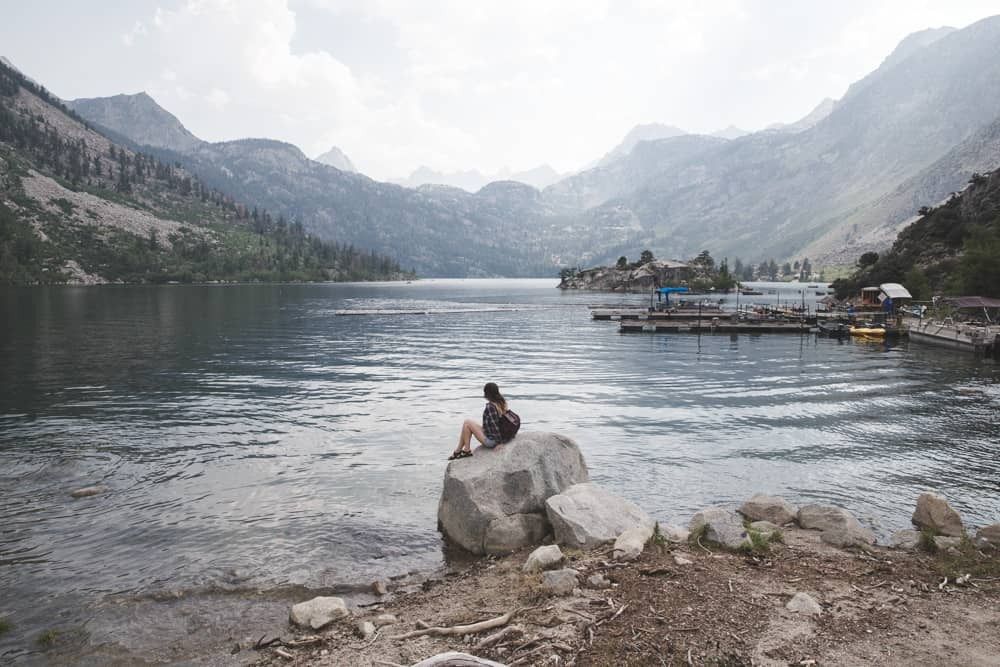 Girl sitting on a rock in front of Lake Sabrina in the Eastern Sierras in California