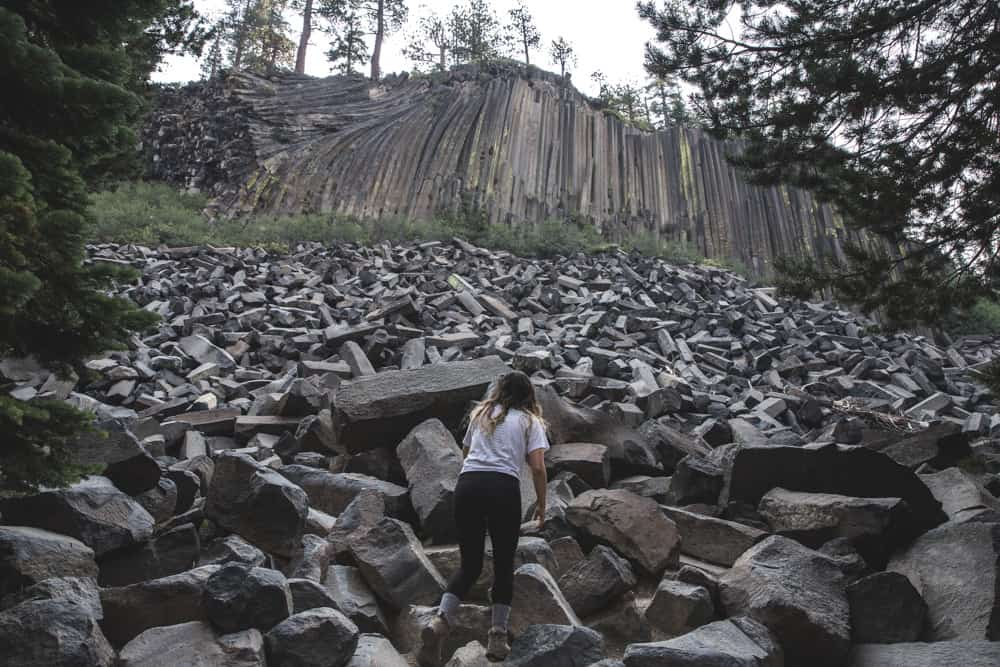 Girl in front of Devils Postpile (large columns and pile of rectangular rocks) surrounded by tall pine trees near Mammoth in the Eastern Sierras in California