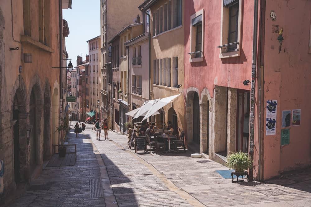 Montée de la Grande Côte, a street in Lyon's Croix Rousse region, is lined with pastel colored pink, orange, and yellow buildings and shops