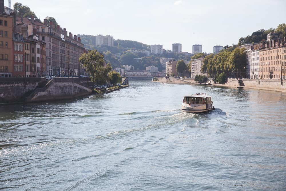 Boat on the Saône River in Lyon, France surrounded by pretty buildings