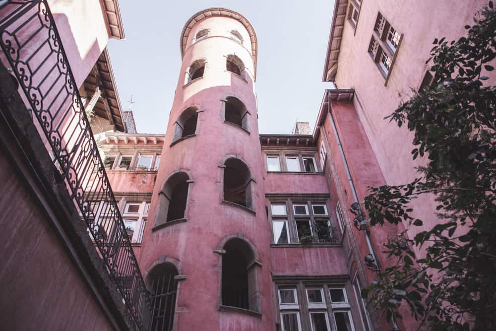 Maison du Crible – Tour Rose is a pink traboule in Old (Vieux) Lyon with a tall round tower and many windows with balconies