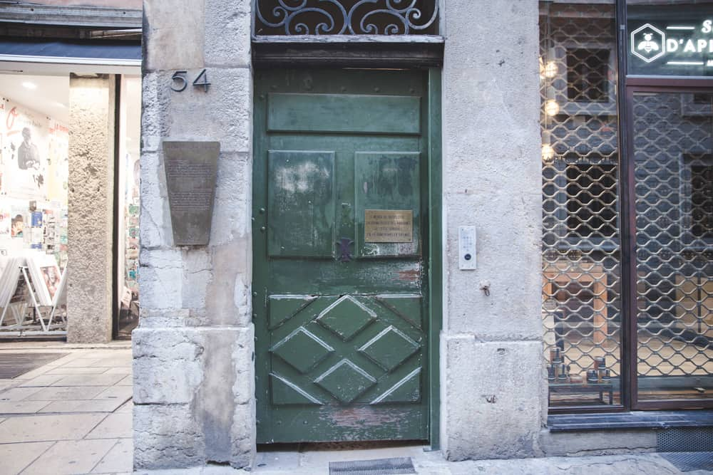 The entrance to a traboule in Old (Vieux) Lyon has a green door and bronze plate that marks the traboule