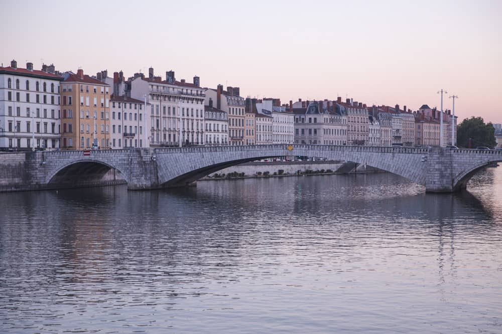 Pastel buildings line the banks of the Saône River at sunset in Lyon, France