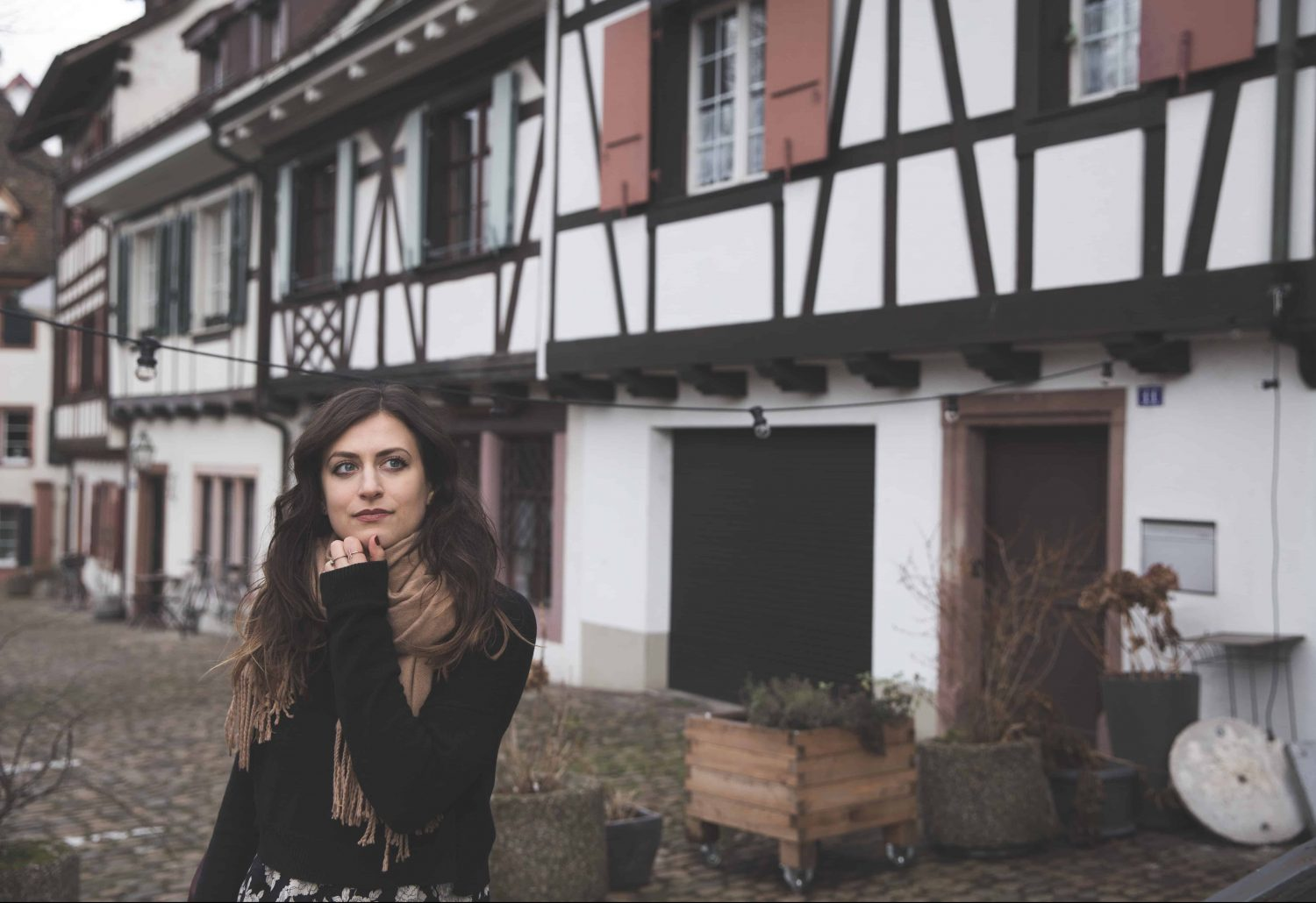 Girl staring into the distance in Basel, Switzerland in front of white and brown half-timbered houses