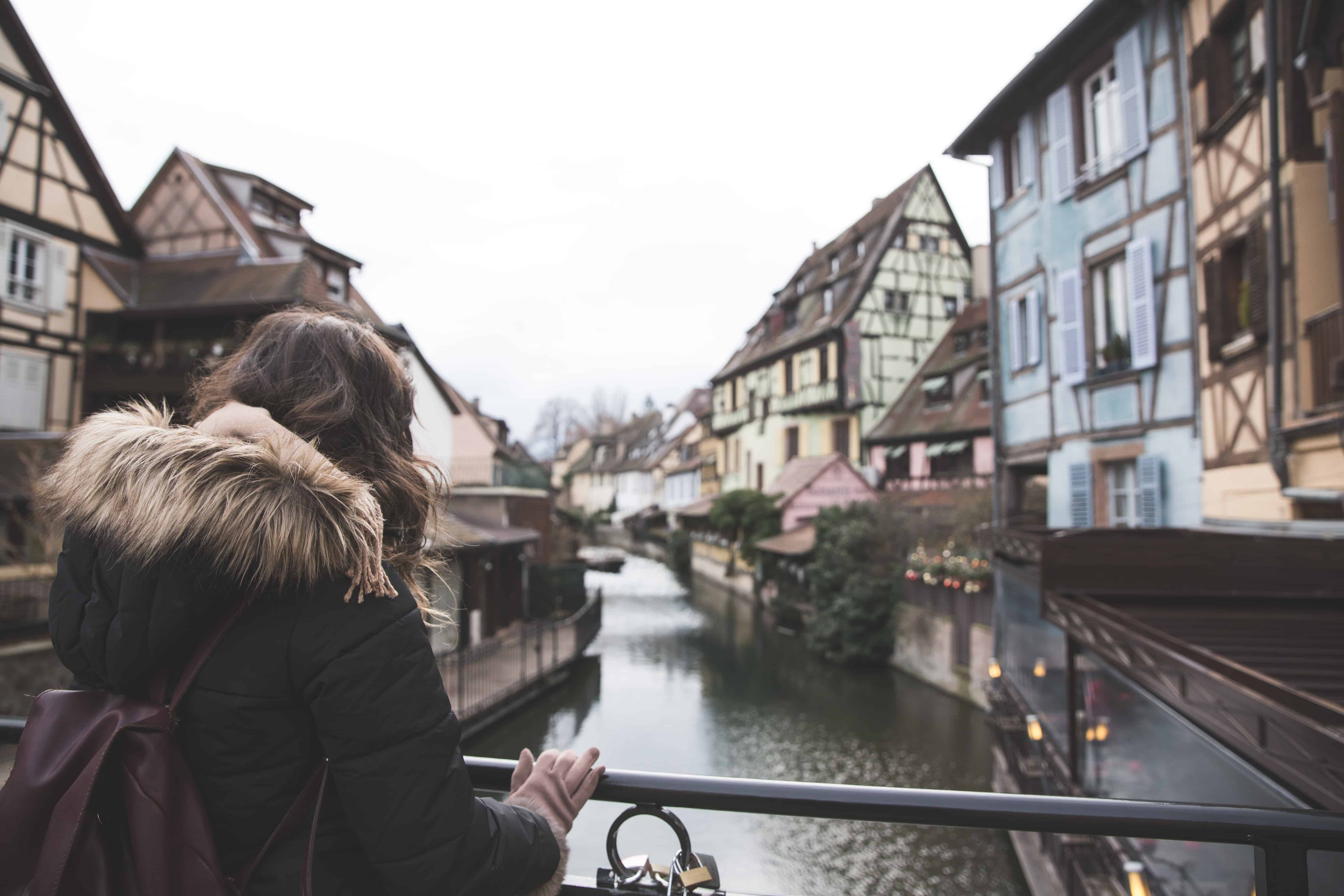 Kelsey looking at colorful buildings along a canal in Colmar, France in winter